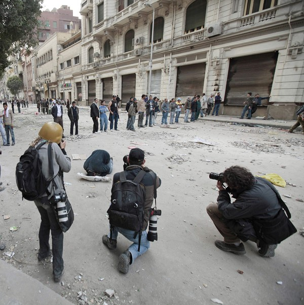 Photographers take pictures of a protestor praying in Tahrir Square.
