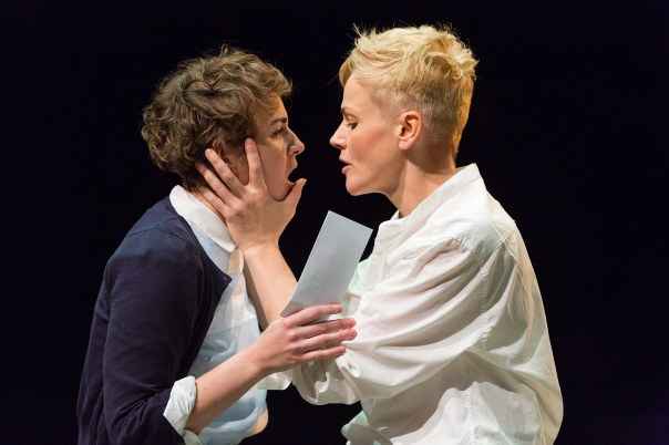 Hamlet on the right grips Ophelia's face.  Hamlet is an androgynous woman.  Ophelia is a young short haired woman.